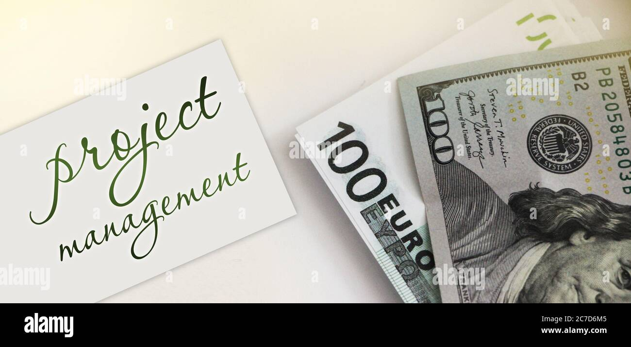 PROJECT MANAGEMENT on card ,100 dollar bill and 100 Euro bill. Business concept Stock Photo