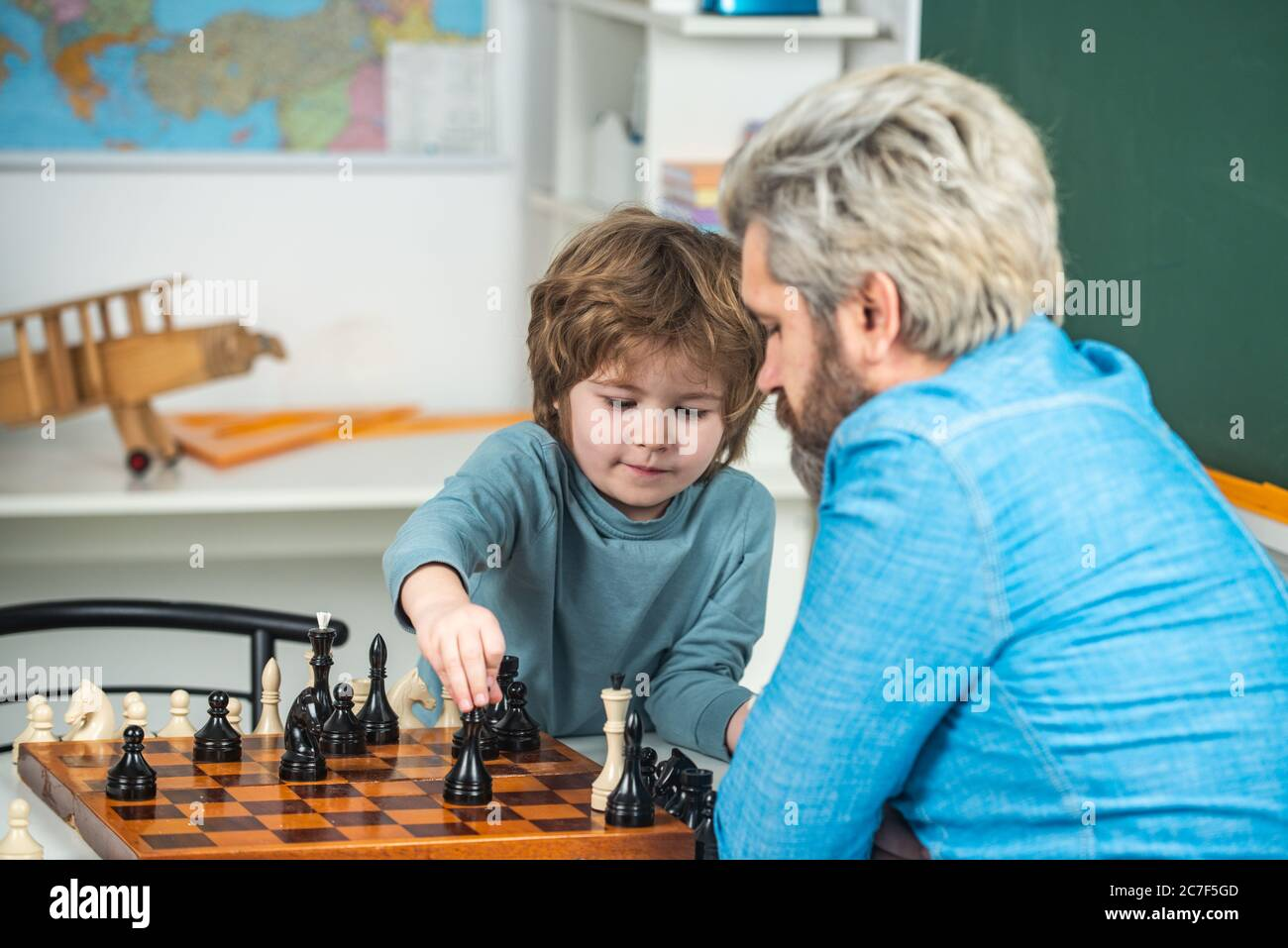 Generations men. Cute little boy playing chess with Parents. Nice concentrated little boy sitting at the table and playing chess with his father Stock Photo