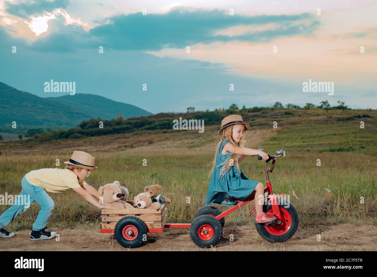 Positive little girl and boy. Little children have fun on fresh air. Walk on countryside. Children play outdoors. While having fun outdoors. Child Stock Photo