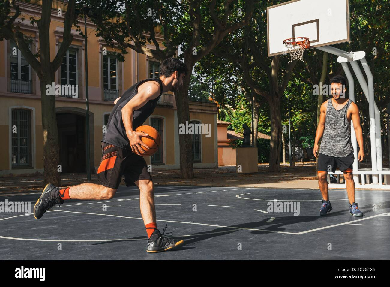 two young men play basketball outdoors Stock Photo