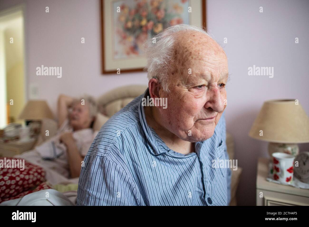 Elderly couple in their 80's sat on the bed in their pyjamas before getting up in the in the morning, England, United Kingdom Stock Photo