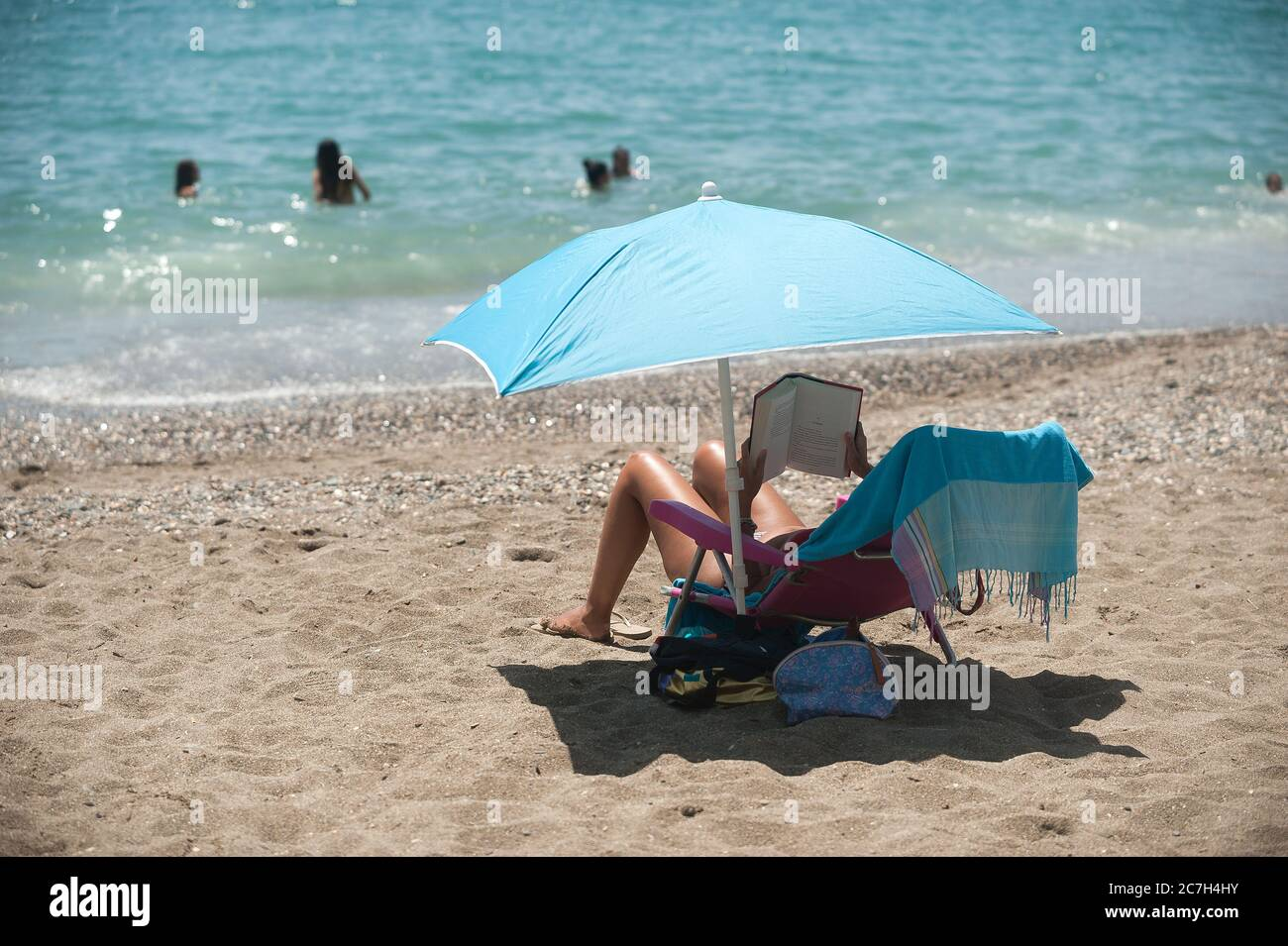 Malaga, Spain. 17th July, 2020. A woman is seen reading a book under an umbrella as she sunbathes at La Malagueta beach amid coronavirus crisis.The appearance of new coronavirus (COVID-19) outbreak in Spain after easing of restrictions has caused the regional government to impose the obligatory use of face masks in outdoors places even when they observe a safe distance between people. This measure tries to curb the spread of coronavirus pandemic. Credit: SOPA Images Limited/Alamy Live News Stock Photo