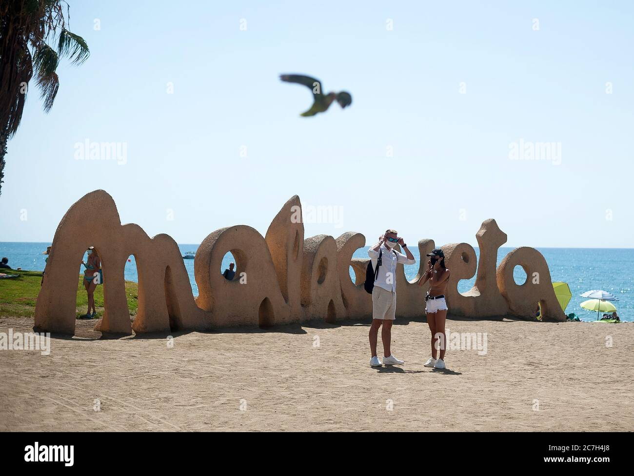 Malaga, Spain. 17th July, 2020. A couple of tourists are seen adjusting their face masks at La Malagueta beach amid coronavirus crisis.The appearance of new coronavirus (COVID-19) outbreak in Spain after easing of restrictions has caused the regional government to impose the obligatory use of face masks in outdoors places even when they observe a safe distance between people. This measure tries to curb the spread of coronavirus pandemic. Credit: SOPA Images Limited/Alamy Live News Stock Photo