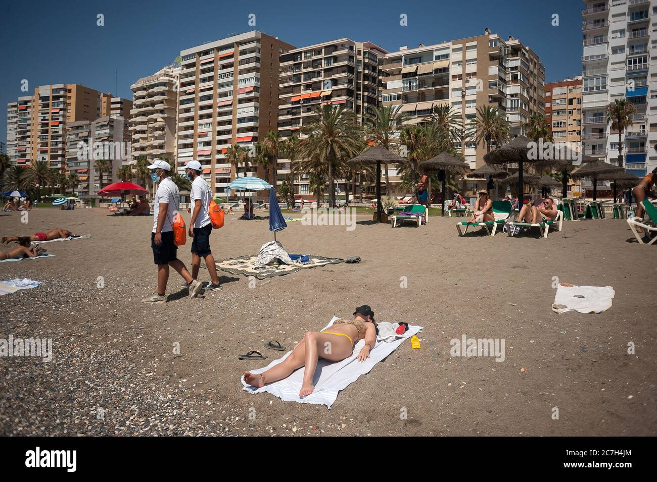 Malaga, Spain. 17th July, 2020. A group of beach assistants wearing face masks walk along the La Malagueta beach amid coronavirus crisis.The appearance of new coronavirus (COVID-19) outbreak in Spain after easing of restrictions has caused the regional government to impose the obligatory use of face masks in outdoors places even when they observe a safe distance between people. This measure tries to curb the spread of coronavirus pandemic. Credit: SOPA Images Limited/Alamy Live News Stock Photo