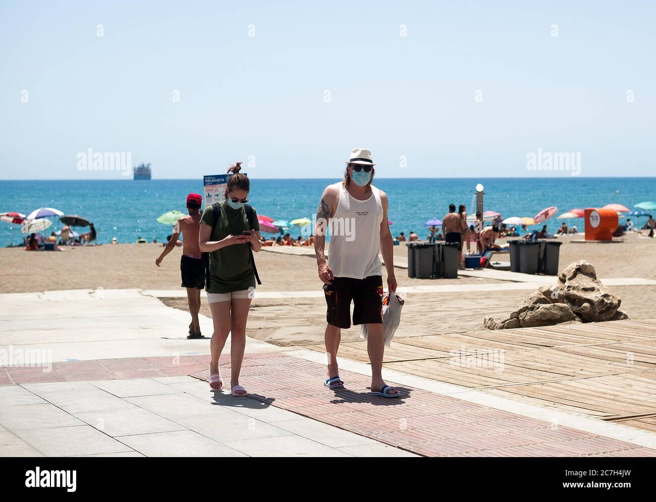 Malaga, Spain. 17th July, 2020. A couple wearing face masks are seen at La Malagueta beach amid coronavirus crisis.The appearance of new coronavirus (COVID-19) outbreak in Spain after easing of restrictions has caused the regional government to impose the obligatory use of face masks in outdoors places even when they observe a safe distance between people. This measure tries to curb the spread of coronavirus pandemic. Credit: SOPA Images Limited/Alamy Live News Stock Photo