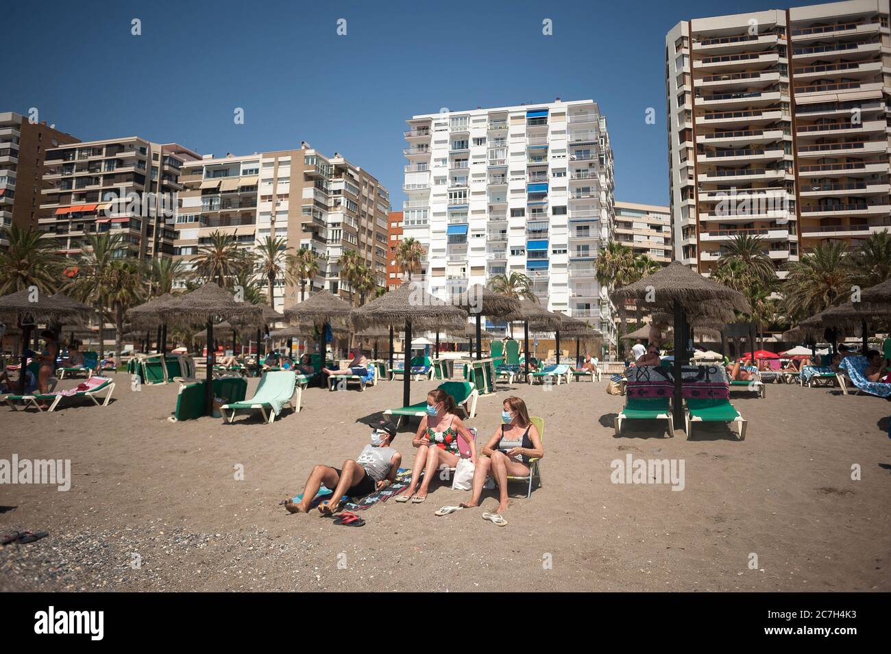 Malaga, Spain. 17th July, 2020. A family wearing face masks seen sunbathing at La Malagueta beach amid coronavirus crisis.The appearance of new coronavirus (COVID-19) outbreak in Spain after easing of restrictions has caused the regional government to impose the obligatory use of face masks in outdoors places even when they observe a safe distance between people. This measure tries to curb the spread of coronavirus pandemic. Credit: SOPA Images Limited/Alamy Live News Stock Photo