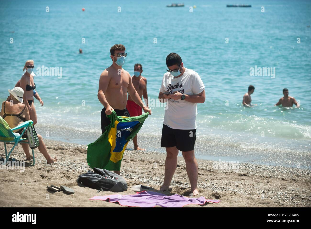 Malaga, Spain. 17th July, 2020. People wearing face masks are seen at La Malagueta beach amid coronavirus crisis.The appearance of new coronavirus (COVID-19) outbreak in Spain after easing of restrictions has caused the regional government to impose the obligatory use of face masks in outdoors places even when they observe a safe distance between people. This measure tries to curb the spread of coronavirus pandemic. Credit: SOPA Images Limited/Alamy Live News Stock Photo