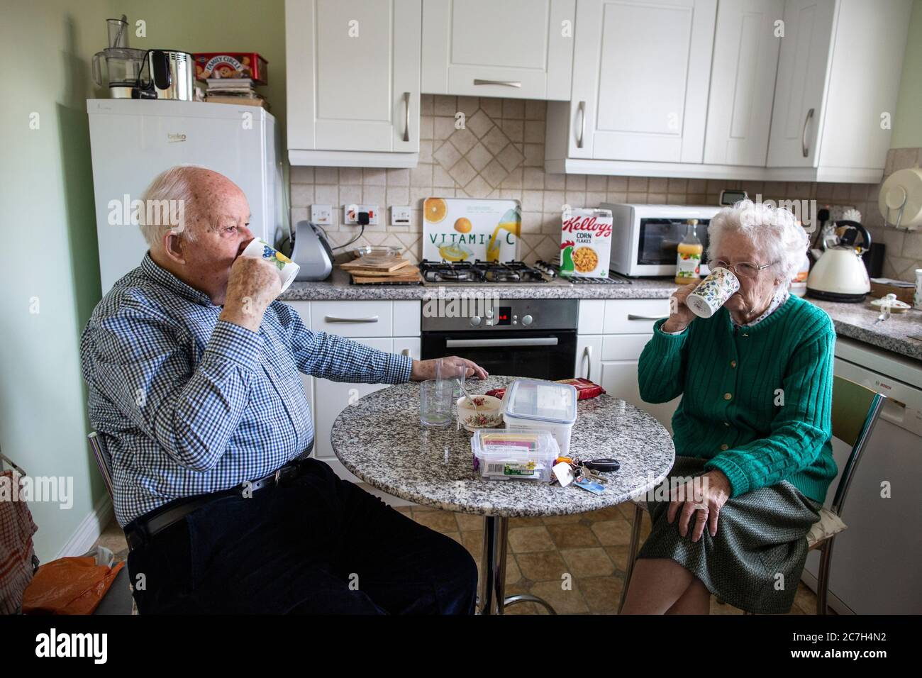 Elderly couple in their 80's taking medication whilst sat at the breakfast table drinking a cup of tea in the morning, England, United Kingdom Stock Photo