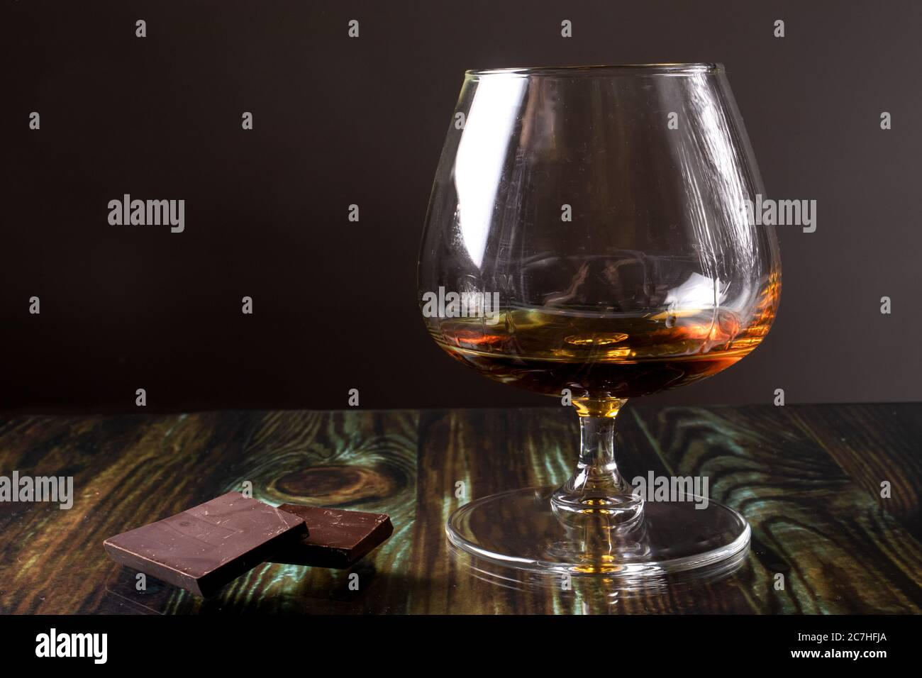 Glass with cognac and dark chocolate. Dear elite alcohol on a dark brown background. Alcoholic drinks. Stock Photo