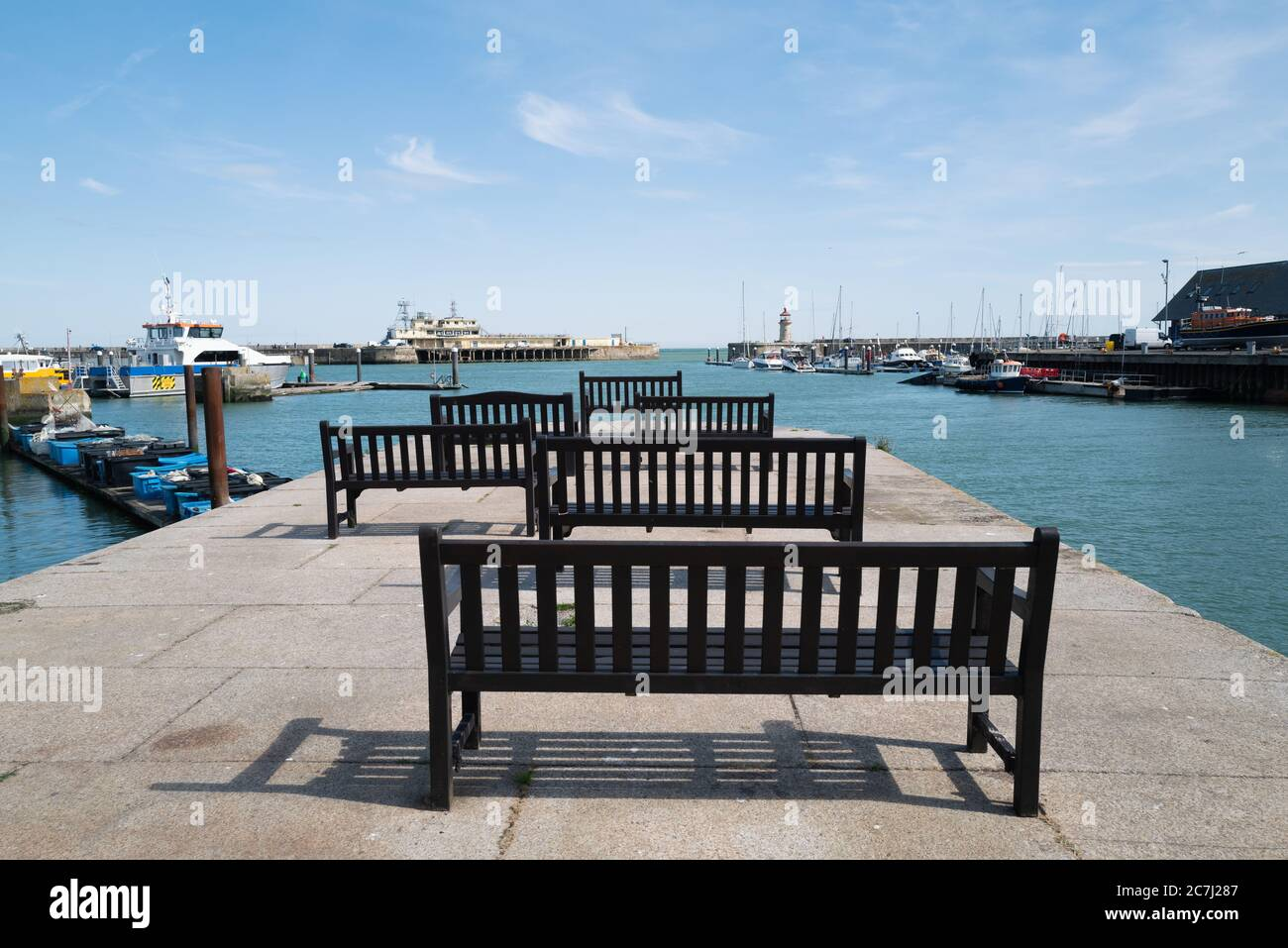 Wooden benches in the Royal Harbour, Ramsgate, looking out towards the lighthouse and an end of pier restaurant Stock Photo