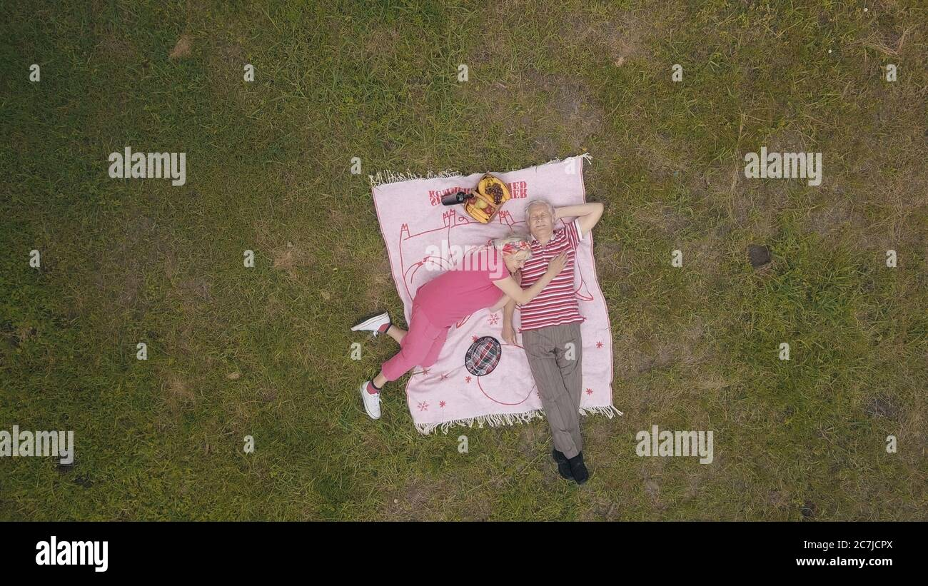 Family weekend picnic in park. Old people, active senior caucasian couple lie on blanket on green grass meadow. Aerial view. Shoot from drone. Elderly man, woman. Celebrating anniversary. Grandparents Stock Photo