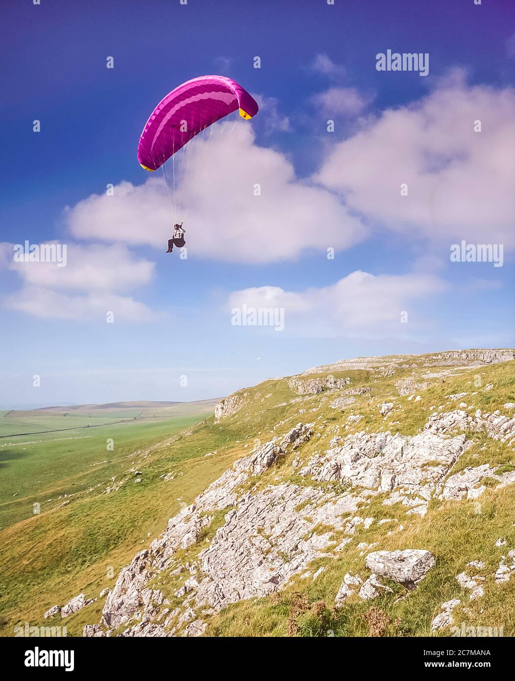 Para gliders ride the thermal air currents rising up over Hunts Cross Scar at Kingsdale not far from the Yorkshire Dales village of Ingleton around 2000 Stock Photo