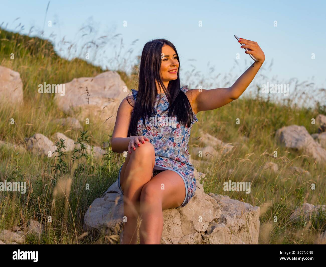 Selfie in nature using hand holding smartphone teengirl is sitting on rock in natural environment slight smile optimistic Stock Photo