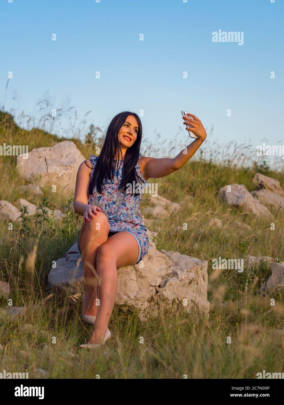 Selfie in nature using hand holding smartphone teengirl is sitting on rock in natural environment legs high heels highheels slight smile optimistic Stock Photo