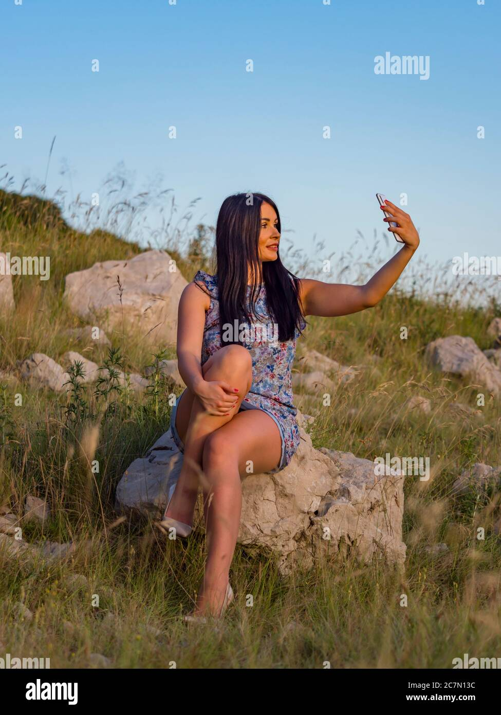 Selfie in nature using hand holding smartphone teengirl is sitting on rock in natural environment legs high heels highheels serious Stock Photo