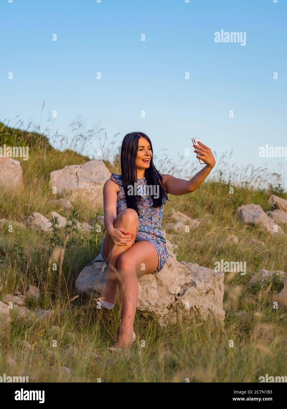 Selfie in nature using hand holding smartphone teengirl is sitting on rock in natural environment legs high heels highheels laughing laugh Stock Photo