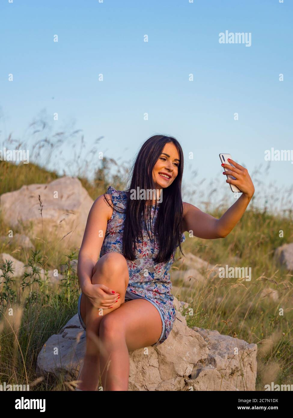 Selfie in nature using hand holding smartphone teengirl is sitting on rock in natural environment smiling smile happy optimistic joy joyful Stock Photo