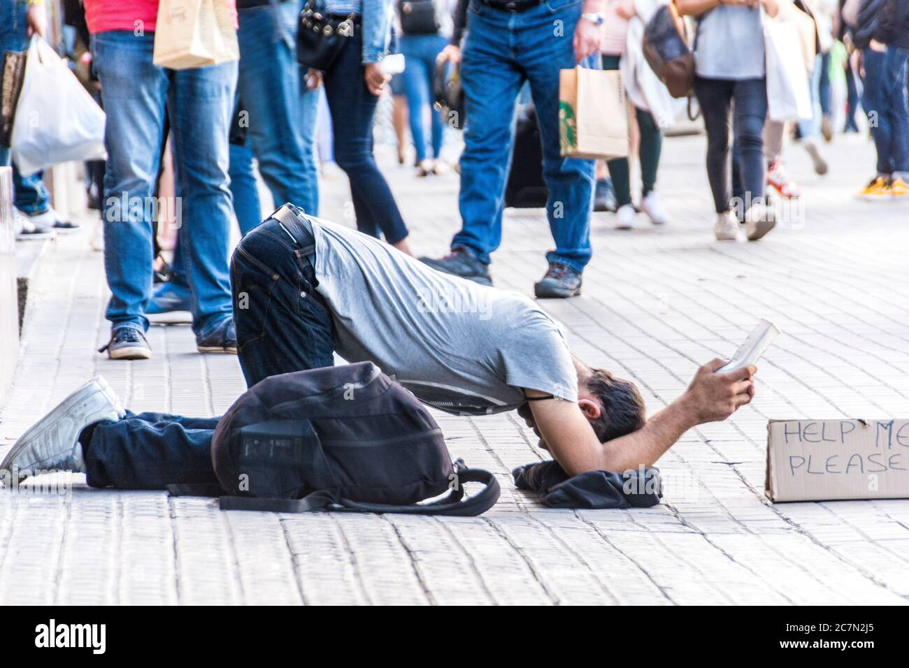 """A homeless young man with a backback with a sign stating, """"Help Me Please,"""" Barcelona, Spain. Stock Photo"""