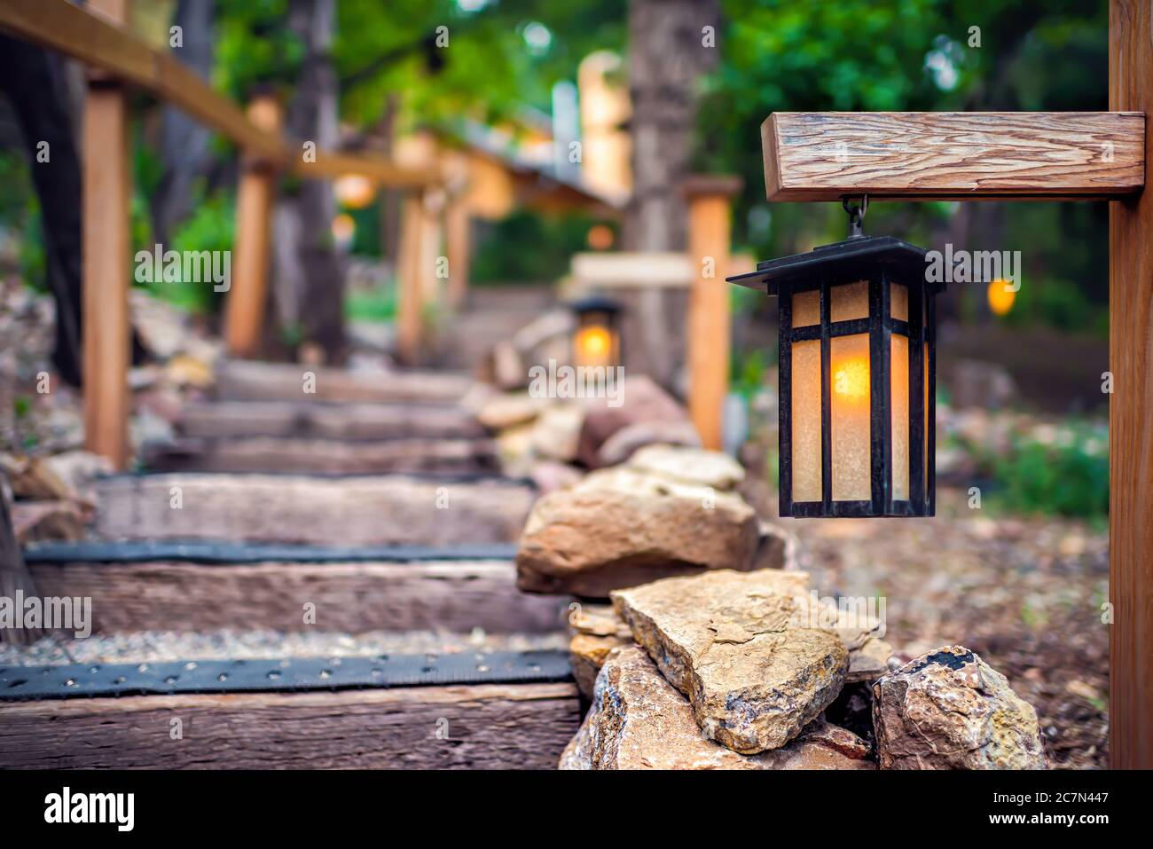 Evening Illuminated Hanging Lantern Lamp Light On Wooden Pole Post In Japanese Garden With Steps Stairs And Green Forest Foliage By Railing Background Stock Photo Alamy