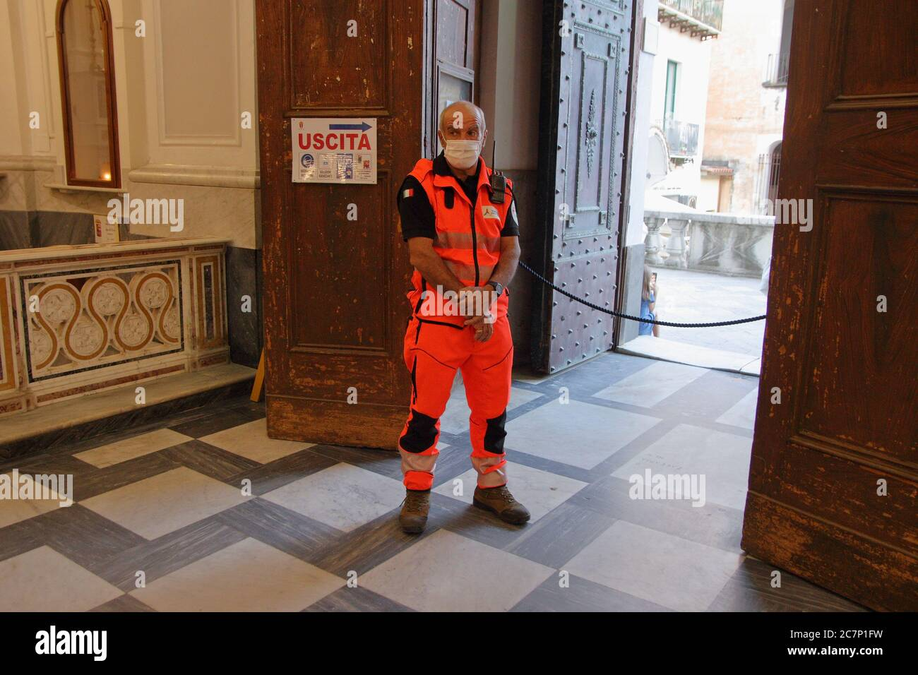A Civil Protection volunteer controls the influx of the faithful inside the Basilica of Santa Trofimena Stock Photo