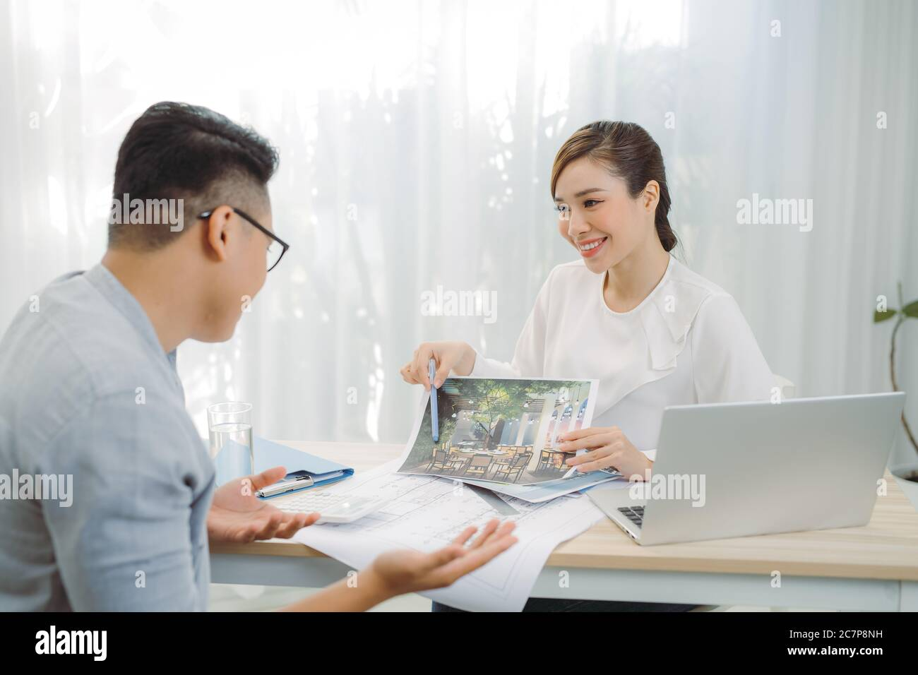 Real-estate agent showing house plans for client at office. Stock Photo