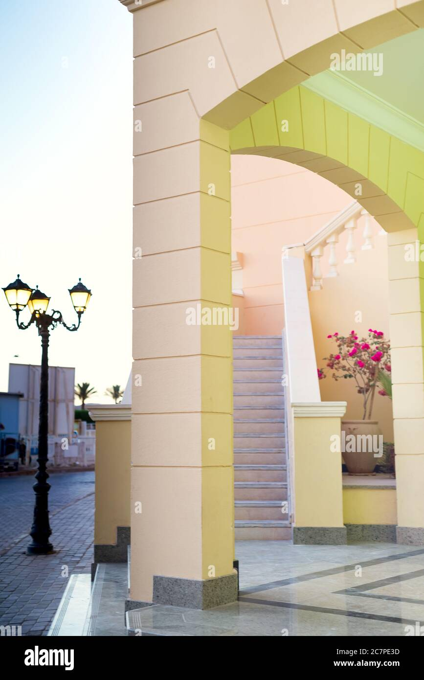 Modern building of hotel with architectural arches, staircace and street lamps near house on a summer sunny day, copy space. Summer travel concept. Stock Photo