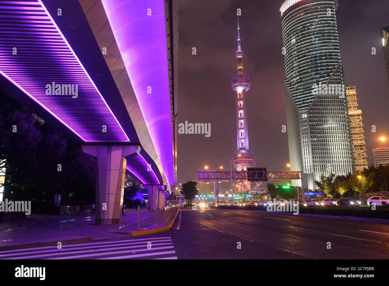 night scene of modern Shanghai Pudong. Highway under shining purple overpass. Famous Oriental Pearl TV Tower and buildings Stock Photo