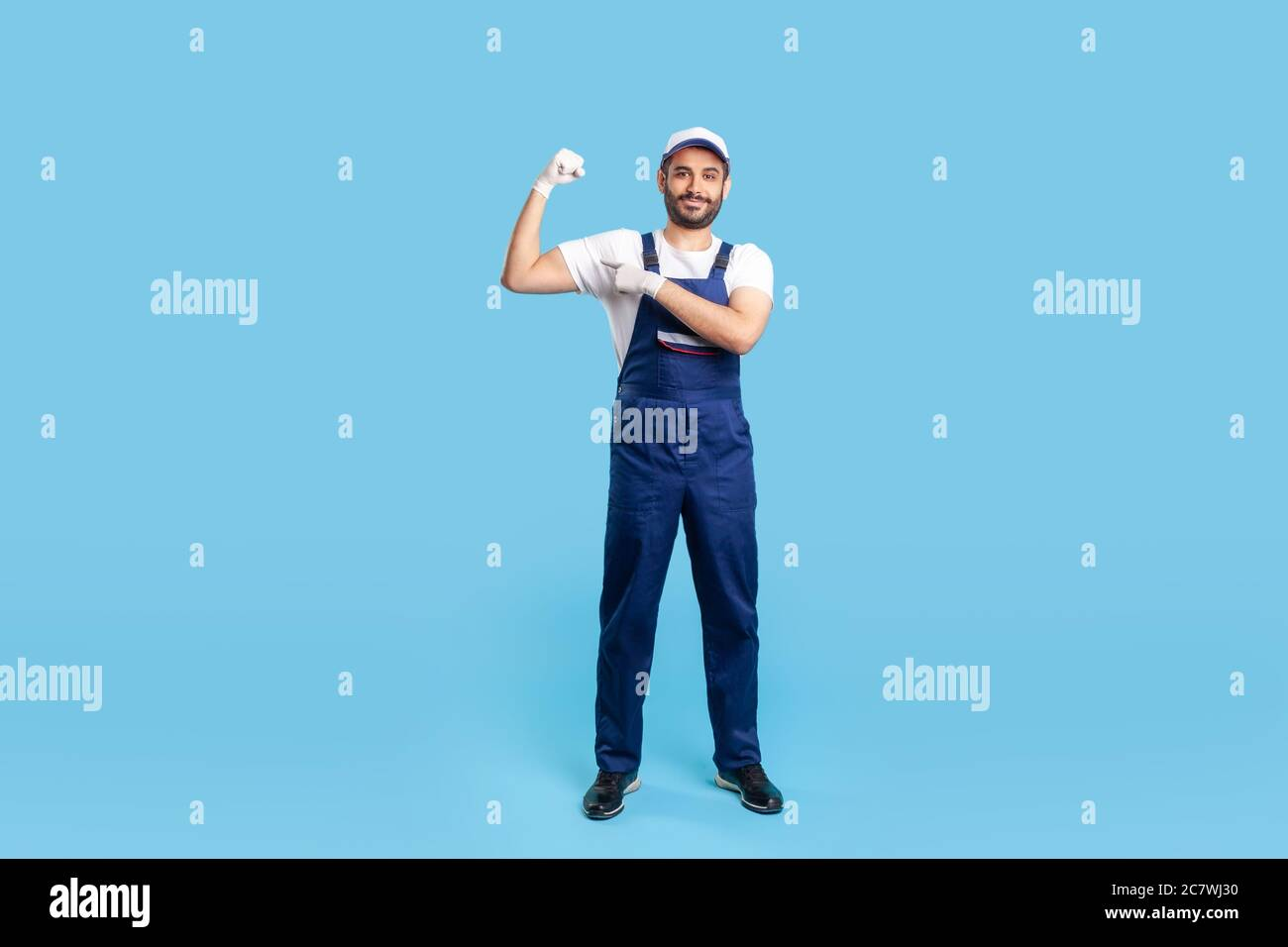 Full length happy expert handyman in blue overalls, cap and protective gloves pointing biceps, demonstrating strength. Profession of service industry, Stock Photo