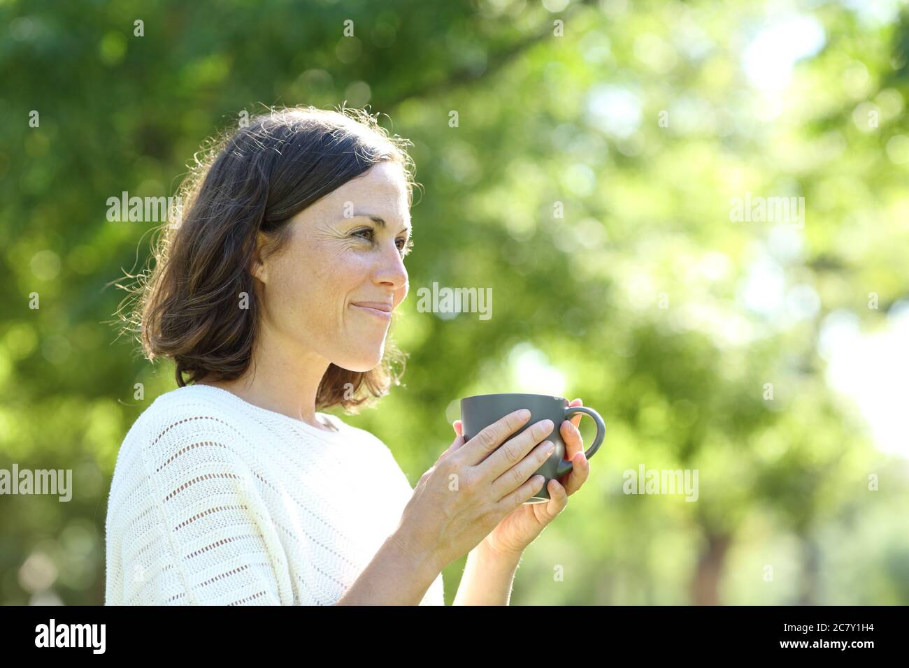 Satisfied adult woman holding a coffee cup standing in the park at summer Stock Photo