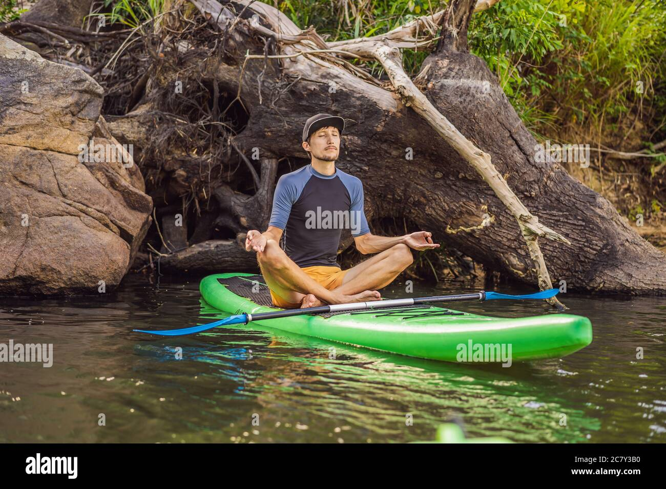 man practicing yoga on a SUP board during sunrise on a large river. Stand up paddle boarding - awesome active recreation in nature Stock Photo