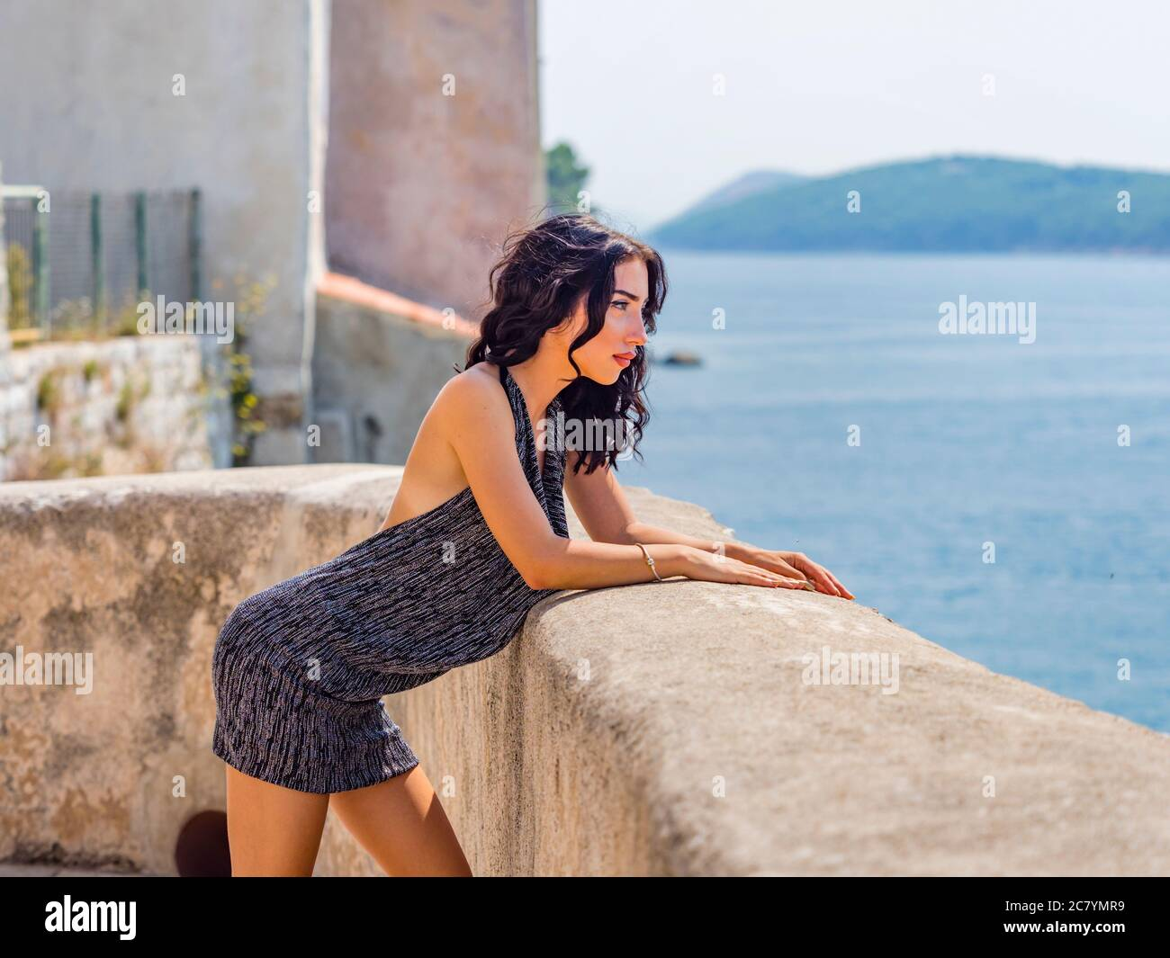 Teengirl inclined on wide stone wall of old medieval town ovelooking sea serious looking away profile sideview side-view bit sexy Stock Photo
