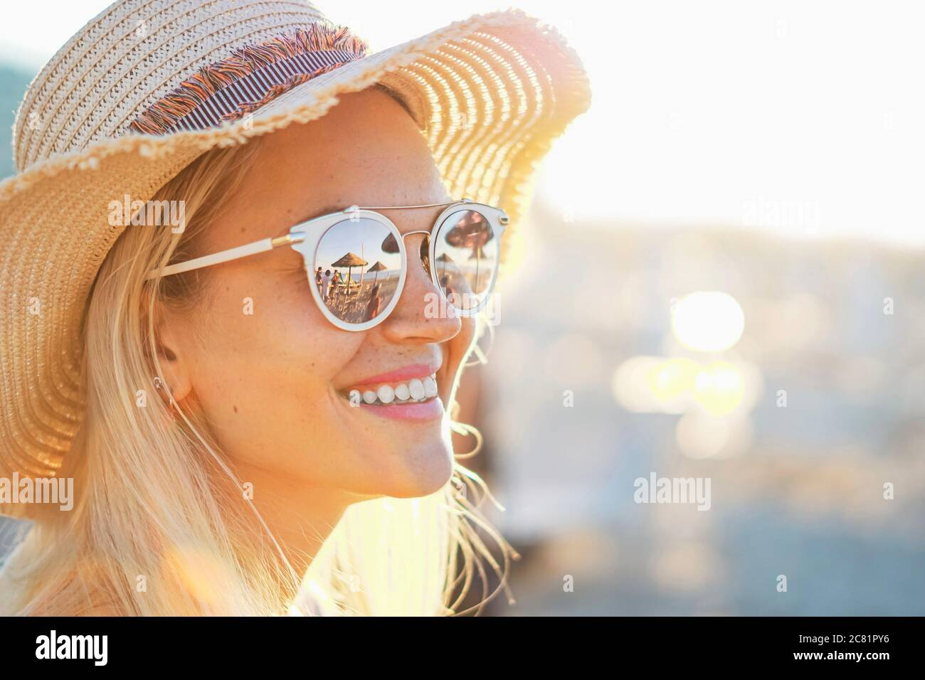 A blonde girl smiling with hat on - Beach and sunlight reflected in sunglasses - Beautiful young women in holidays - Portrait photo Stock Photo