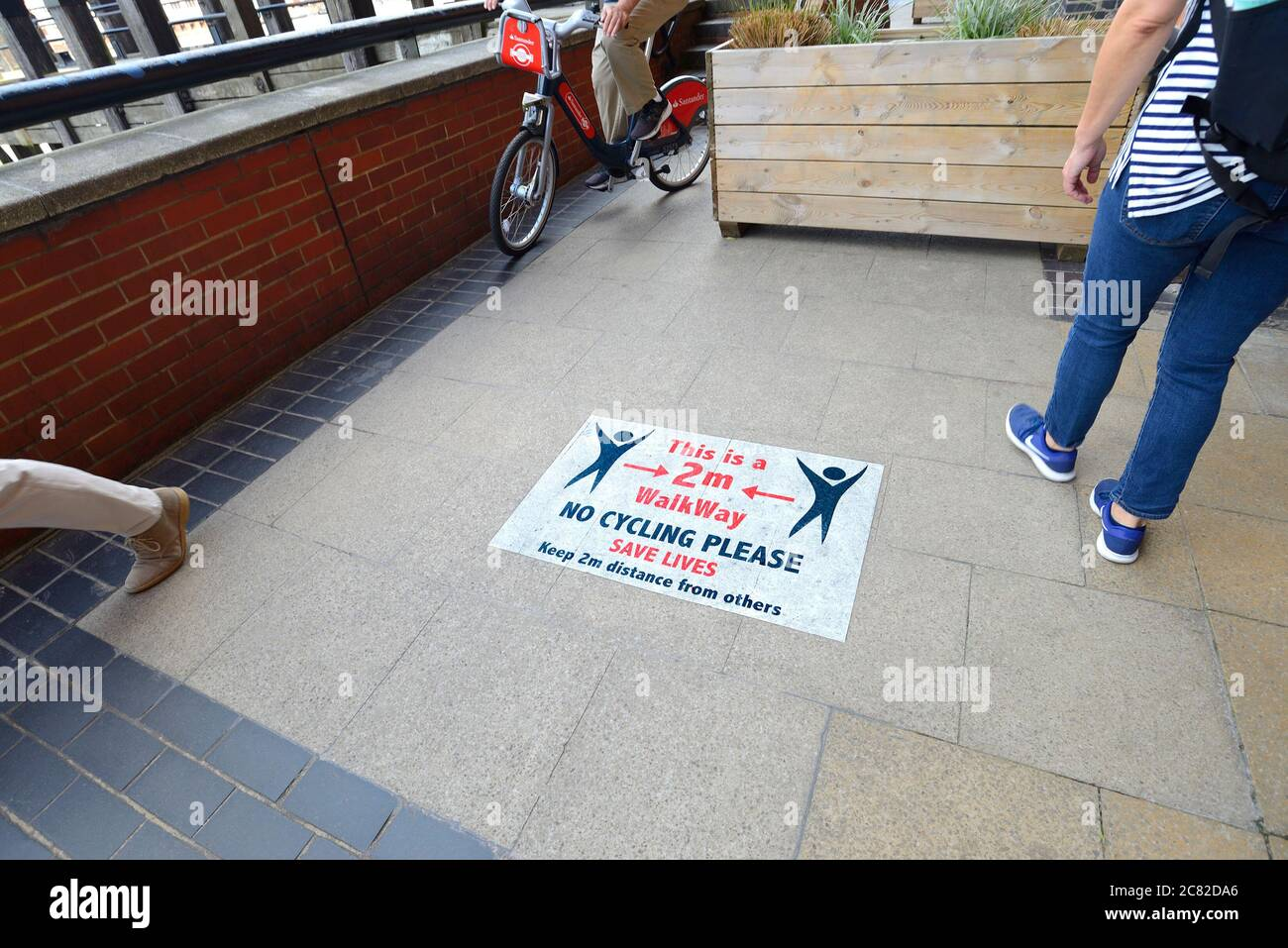 London, England, UK. COVID-19 precautions on the South Bank. Signs advising social distancing and no cycling - cyclist ignoring the signs Stock Photo