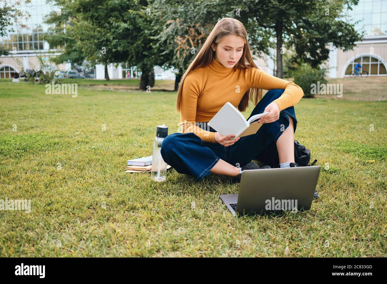 Beautiful casual student girl reading book studying with laptop on lawn in city park Stock Photo - Alamy