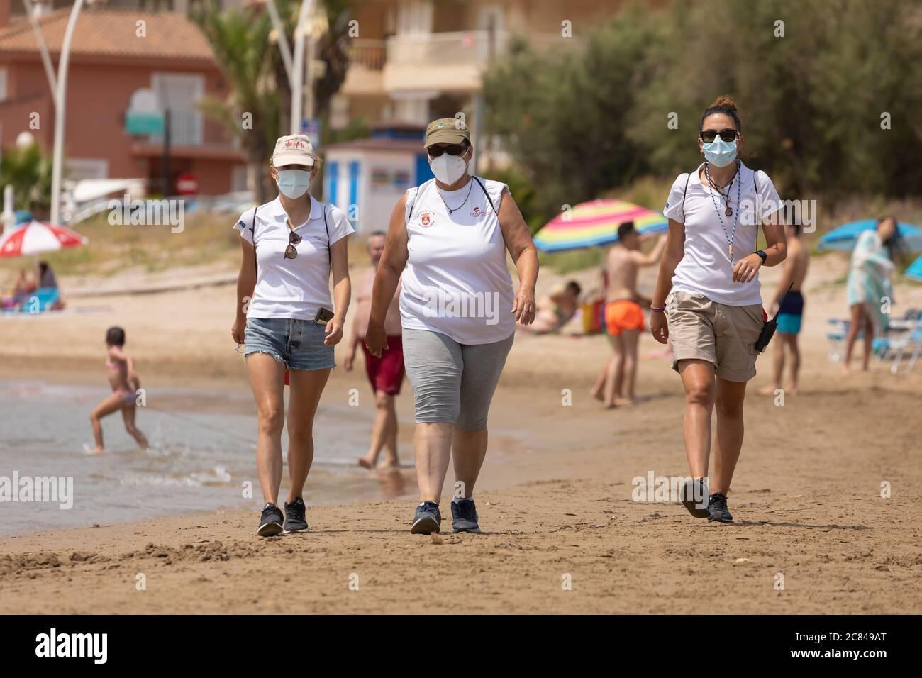 Torrenostra, Castellon, Spain - July 16, 2020: Beach assistants and attendants, work on the beach informing to help beachgoers to prevent coronavirus. Stock Photo