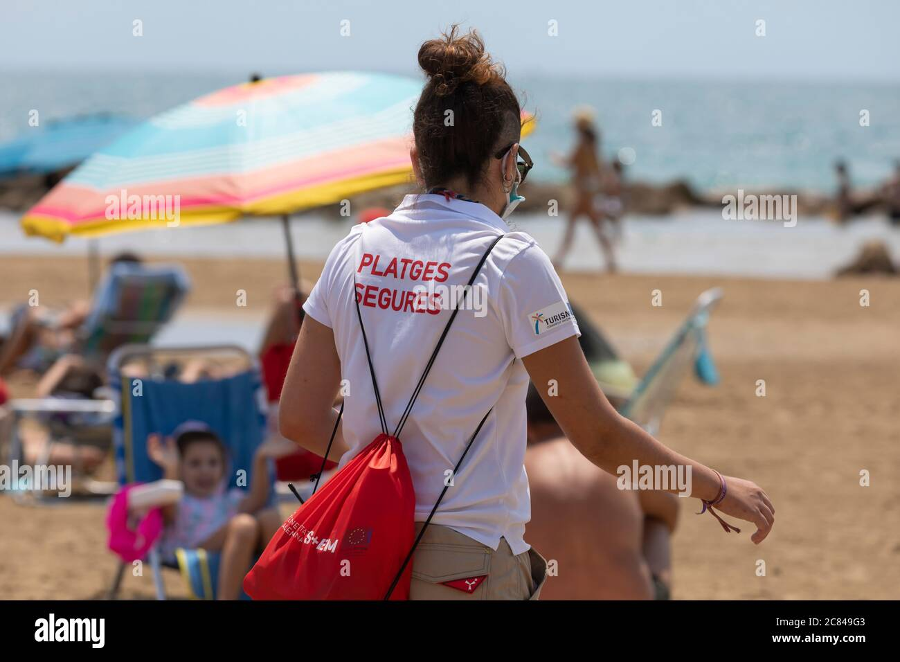 Torrenostra, Castellon, Spain - July 16, 2020: Beach assistants and attendants, work on the beach informing to help beachgoers to prevent coronavirus. Stock Photo