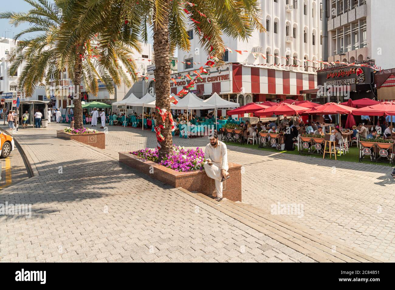 Mutrah, Oman - February 10, 2020: People enjoying a outdoor bars and restaurants in the center of Mutrah in a hot day, province of Muscat, Sultanate o Stock Photo