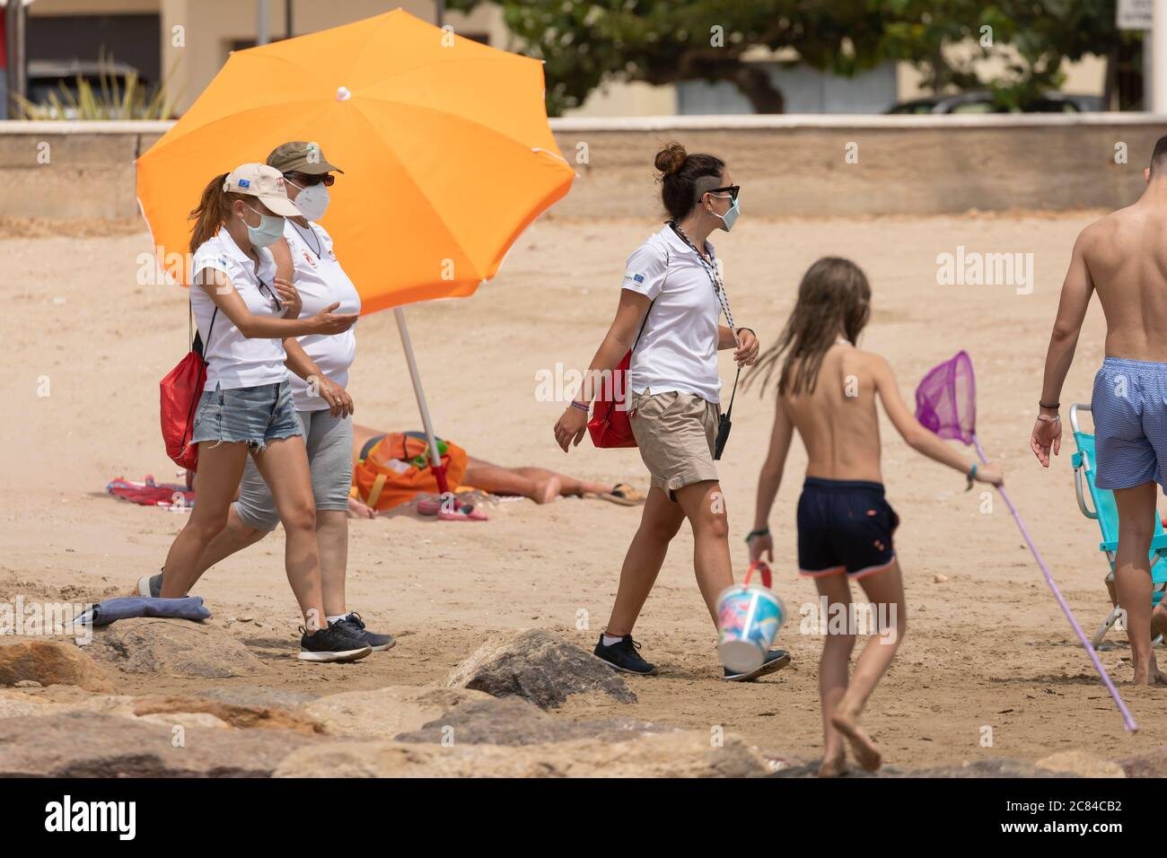 Torrenostra, Castellon, Spain - July 16, 2020: Beach assistants and attendants, work on the beach informing to help beachgoers to prevent the spread o Stock Photo