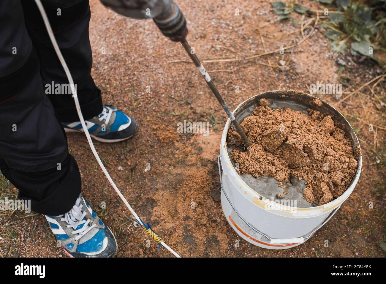 Preparation of cement glue mortar in a bucket of cement and sand using a mixer nozzle on a drill - the work of a professional bricklayer Stock Photo