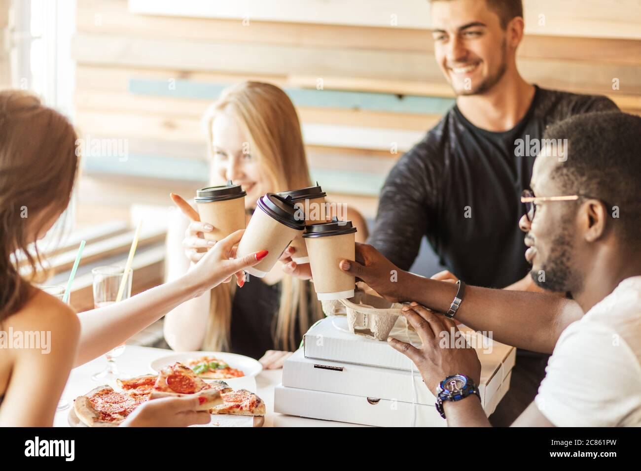 Group of young multiracial friends hanging out at a coffee shop. Young men and women meeting in a cafe having fun, eating pizza and drinking coffee Stock Photo