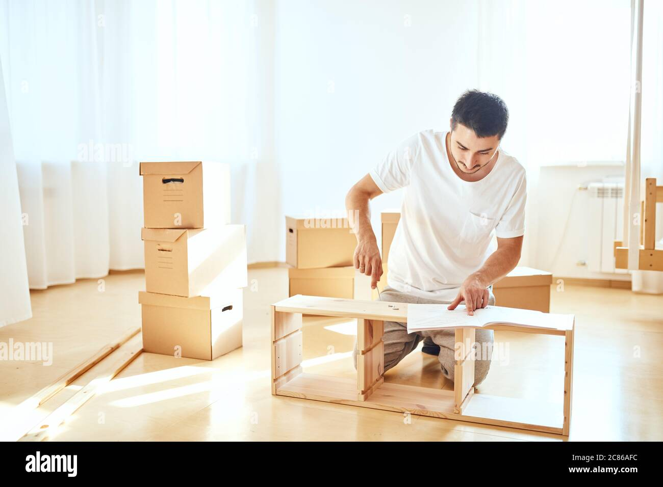 Concentrated Young Man Reading Instructions To Assemble Furniture At Home Stock Photo Alamy