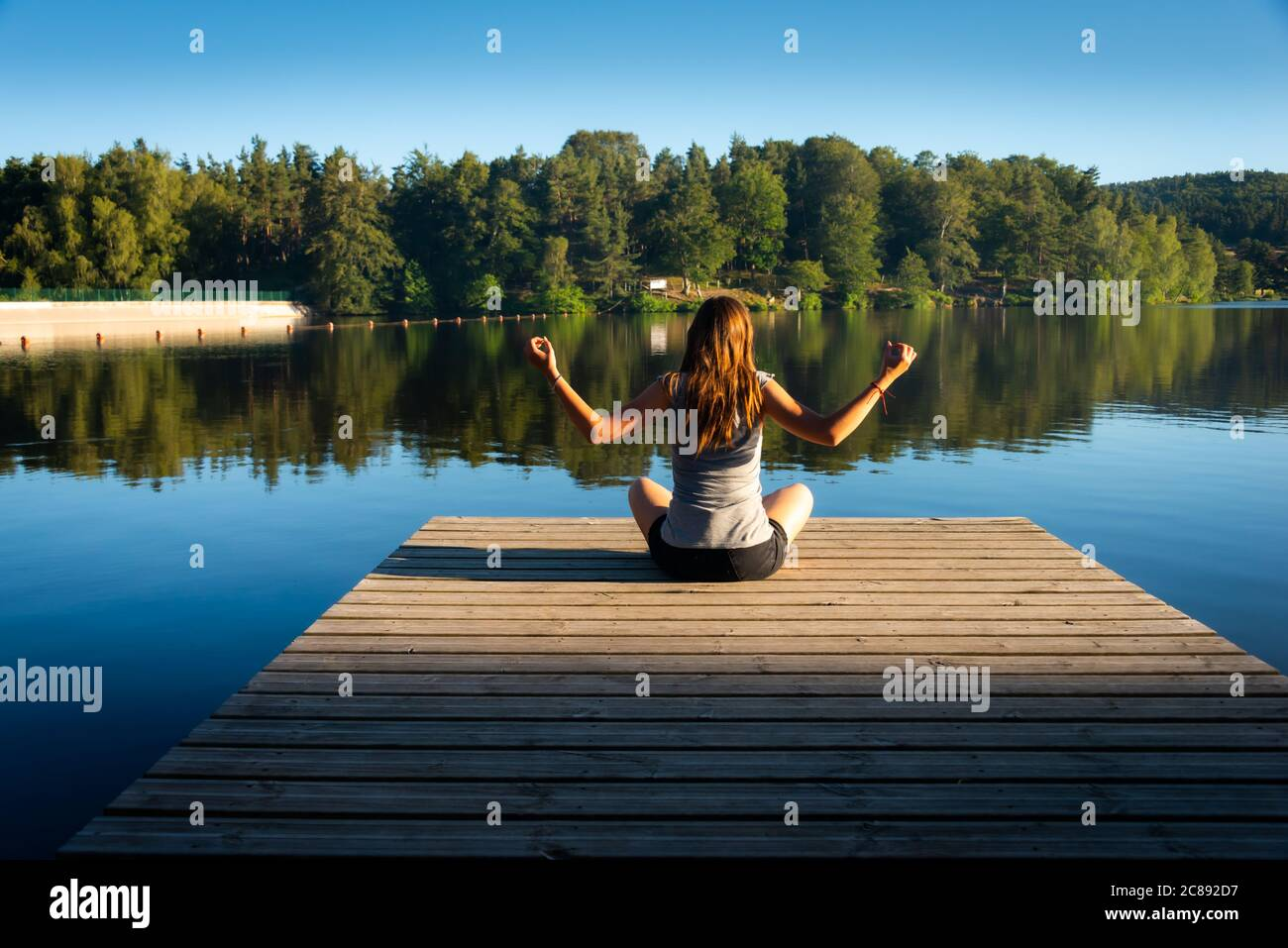 young woman on wooden pontoon or pier  practicing yoga & relaxing on holiday . Stock Photo
