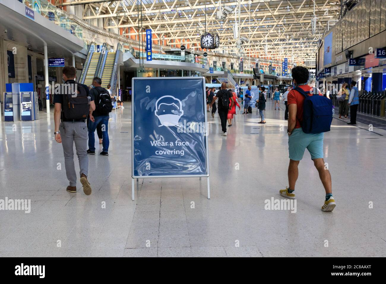 "London, UK. 22nd July, 2020. A ""Wear a Face Covering"" sign reminds commuters inside Waterloo Station to wear their masks. Mask wearing and social distancing appear to become 'the new normal' as more and more people get used to the new guidelines and recommendations in place. Credit: Imageplotter/Alamy Live News Stock Photo"