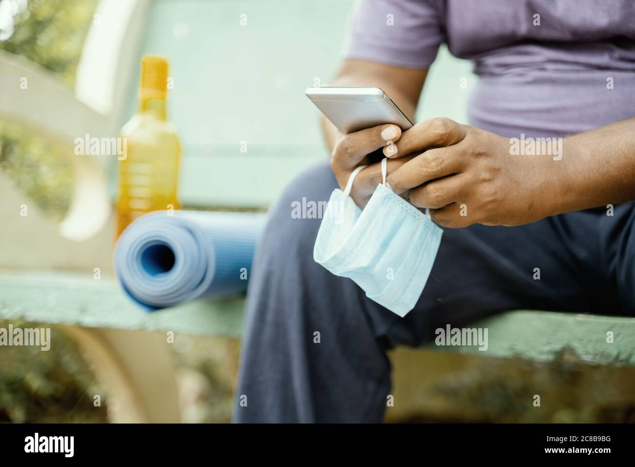 Man using mobile with mask in hand at park during morning yoga or workout with mat - concept of coronavirus or covid-19 advice, protection or to Stock Photo