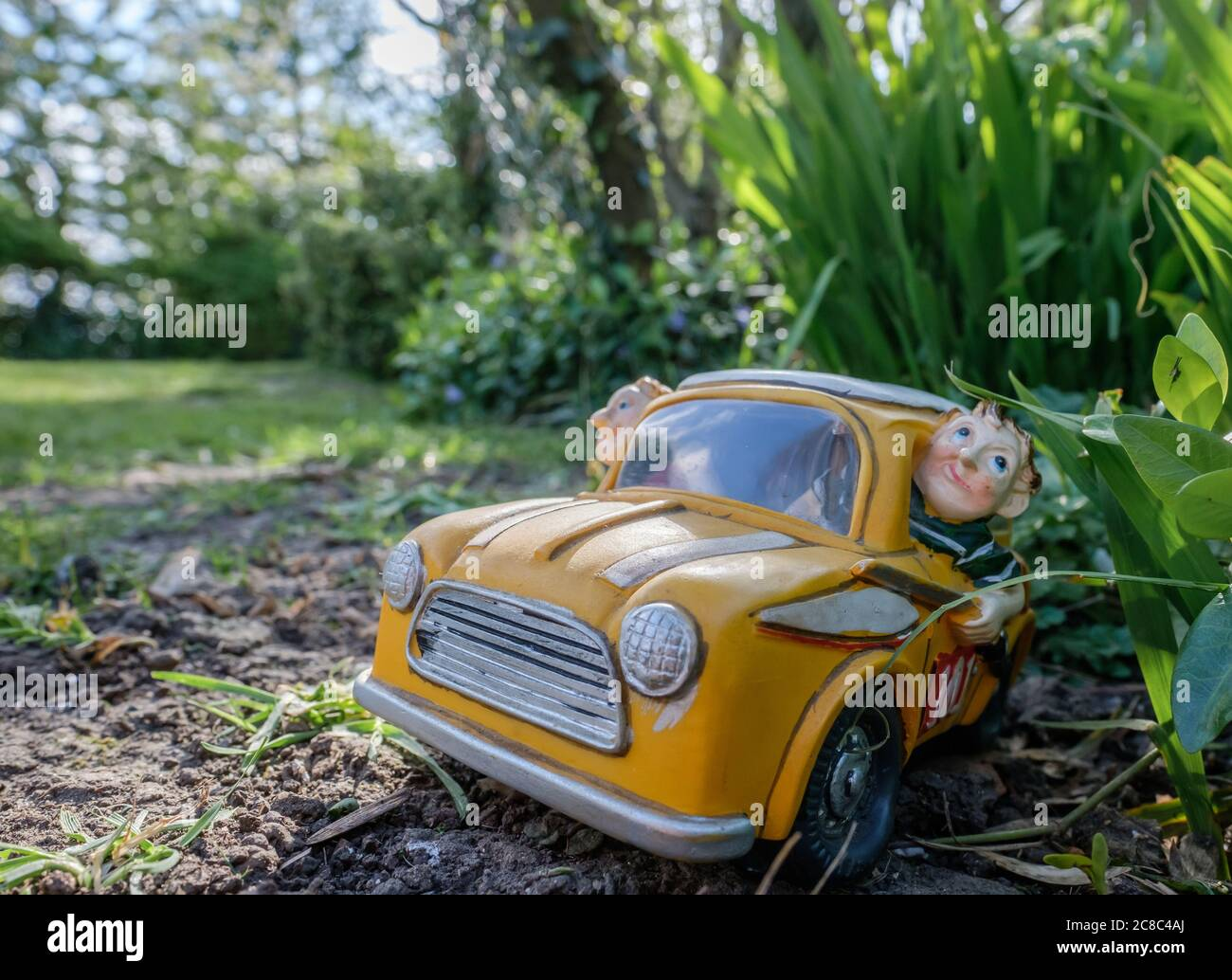 Miniature, ceramic styled small model of a hatchback car shown in various positions in a large, residential garden. Stock Photo