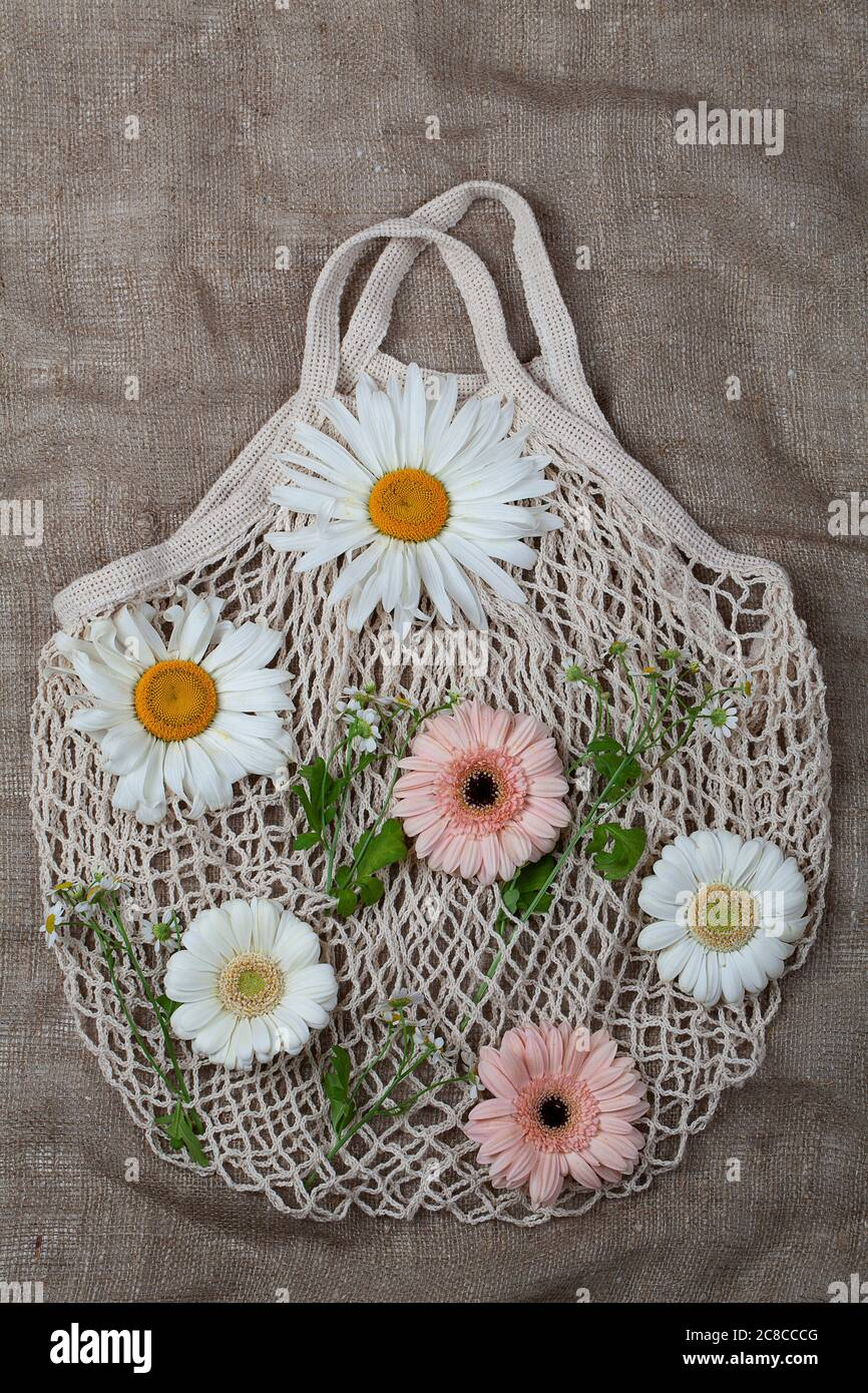 Eco-friendly reusable white cotton mesh bag with fresh flowers on brown background Stock Photo