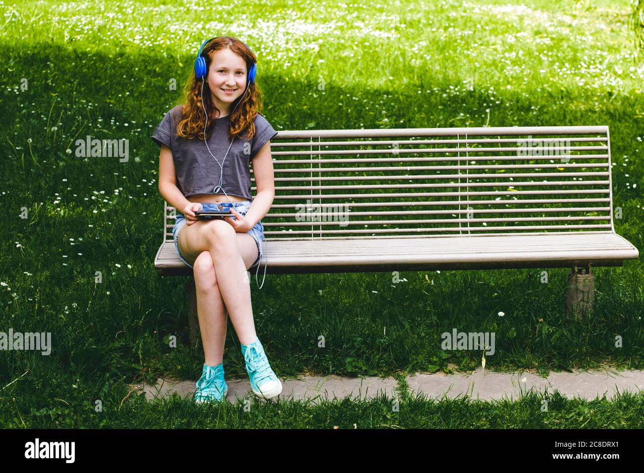 Smiling girl listening music through headphones while sitting on bench at park Stock Photo