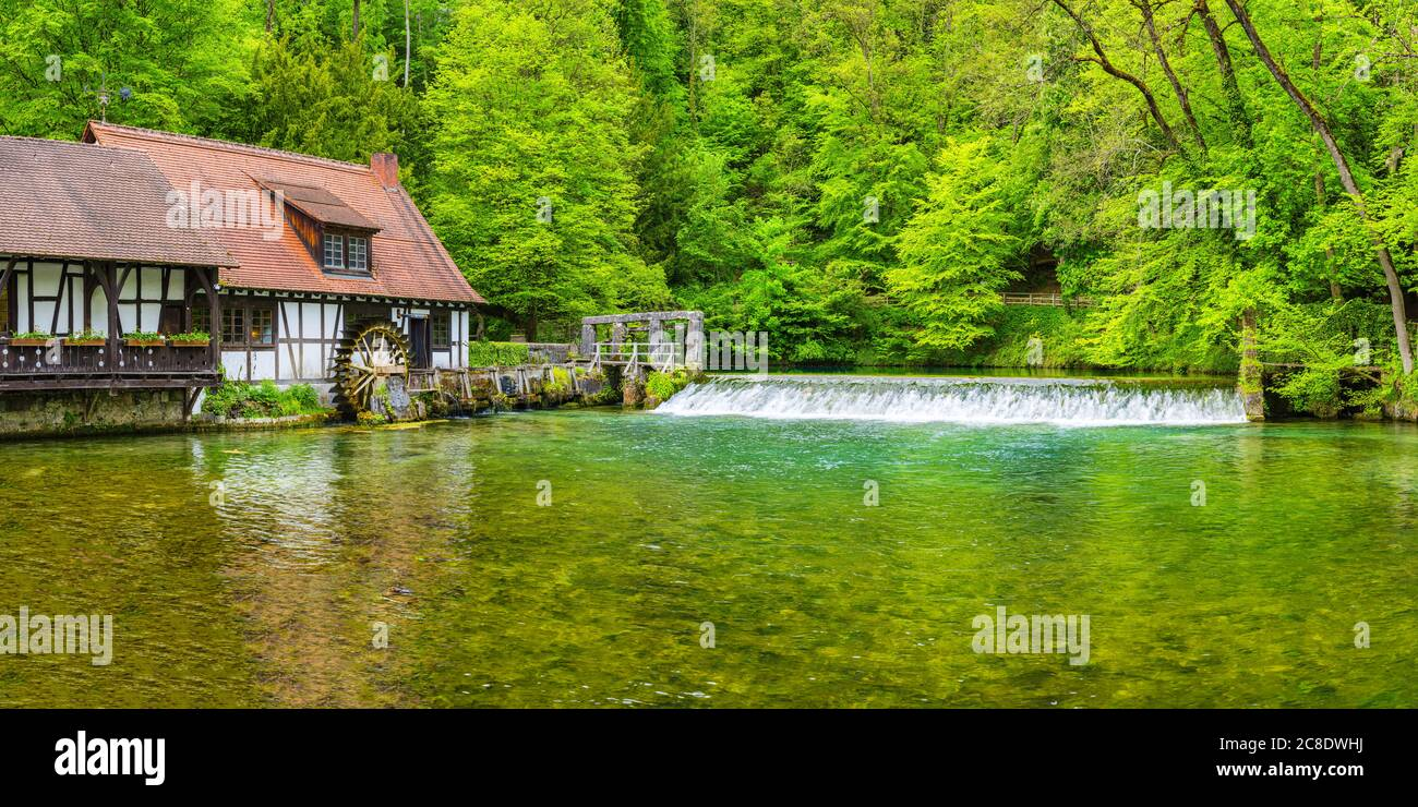 Germany, Baden-Wurttemberg, Blaubeuren, Rustic house on forest riverbank in spring Stock Photo