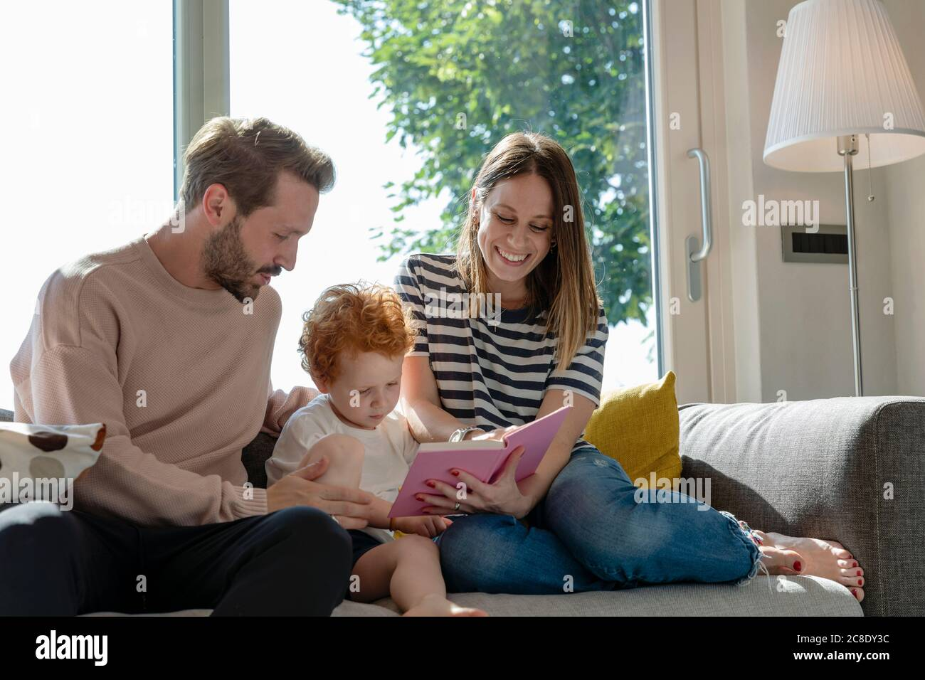 Smiling woman reading picture book while sitting by son and man on sofa in living room at home Stock Photo