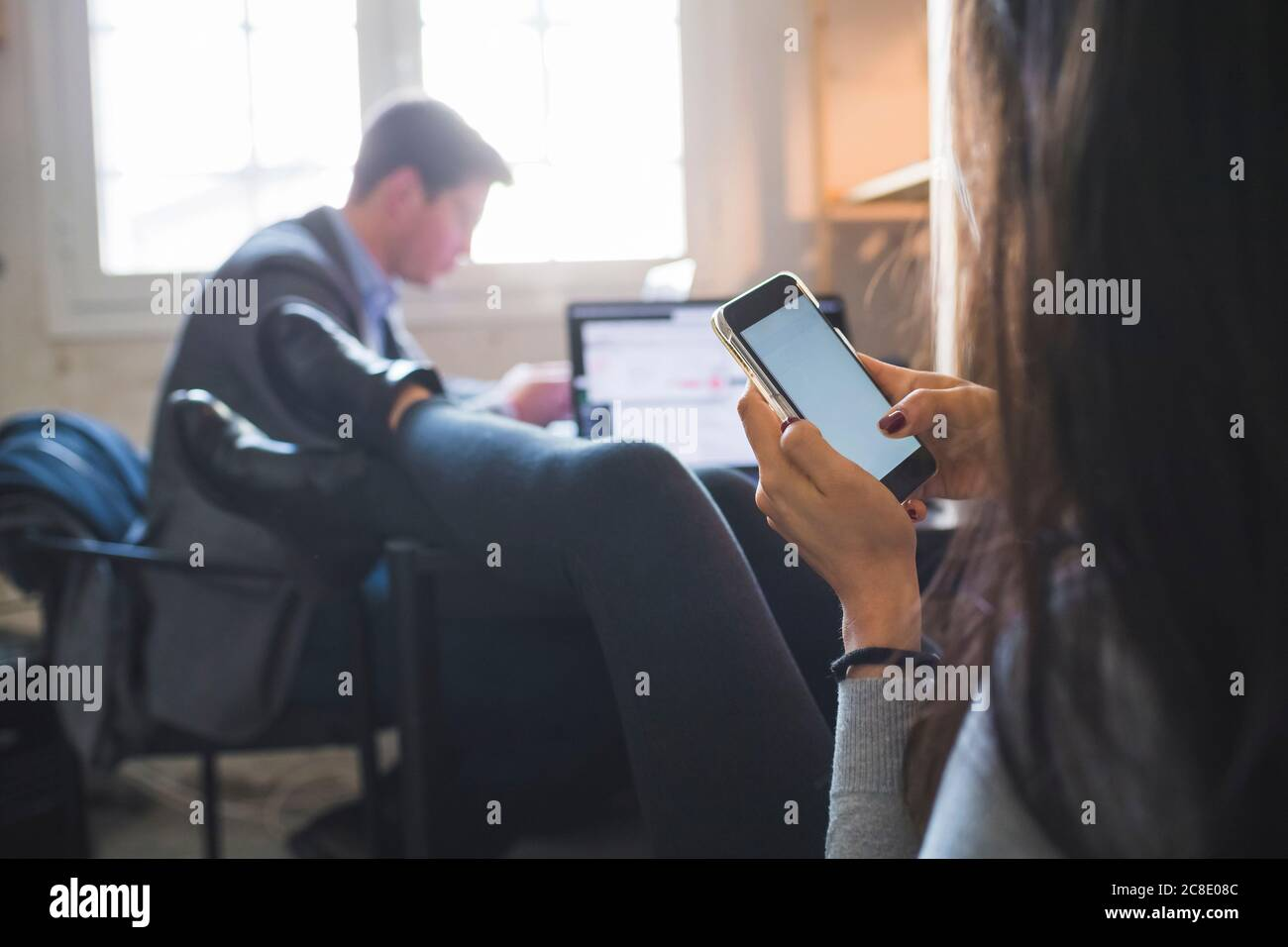 Relaxed woman using smartphone at desk with businessman in background working Stock Photo